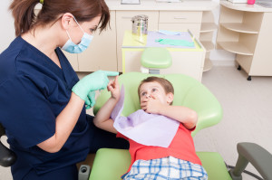 Woman dentist calming kid patient with games