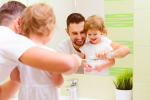Father helping young daughter brush teeth