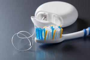 Some floss and a toothbrush with each other