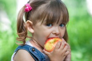 A girl takes a bite out of an apple.